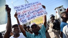 https://www.pinterest.com/jjerome958/eve-the-2020-global-initiative-for-news-on-haiti/ Demonstrators hold up signs during a protest near the parliament in Port-au-Prince, on December 8, 2016