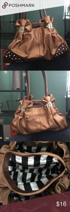 Gold/Bronze Charming Charlie's Purse Cute modern purse to spruce up your outfit. The bronze gold bag has small detailing that will make any outfit shine. Purse has 3 sections for organizing and has a nice clean black and white striped inside. Charming Charlie Bags Shoulder Bags