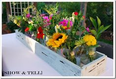 fresh cut flowers in mason jars in rustic wood container