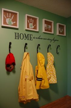 Black coat hooks hung on the wall with DIY handprint art of the family