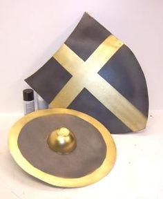 For round shield, maybe glue two circles of cardboard crisscrossed in either direction for reinforcement. Cut and piece of poster board into a Celtic knot, paint and glue onto shield. TP rolls wrapped in duct tape fastened to the inside for handles.