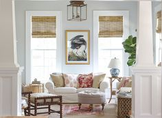 Beautiful living room by Holly Mathis and photographed by Becki Griffin. I love how fresh this space looks. It's updated and timeless all at the same time. Really pretty living room with bamboo Roman Shades, white slip-covered sofa, layered rugs, a beautiful lantern and pale gray-blue walls.