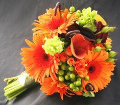 Orange Gerber daisies, dark purple mini callas, green coffee bean, Fiddle Fern and Bells of Ireland wedding bouquet.