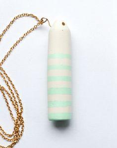 Peralia_Collana con pendente cilindrico in ceramica bianca a righe colorate. Il colore applicato viene steso dopo la cottura ed è uno smalto ad acqua color verde gemma.