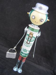Mr. Herb Ox Bot by ckudja #1370 This little bot gets his name from vintage Herb-Ox bouillon cubes. His arms are old scrap tools, His cute little face is made with a mini pool ball. His hat is little recessed closet or leaver door pulls. His facial features are made with an assortment of scrap jewelry and hardware. He wears a tie made from some random part. He holds a briefcase made out of two folding opera glasses.