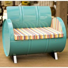 Add some green furniture to your life. We recycle and repurpose used steel drums into striking designs. This 55-gallon drum is recycled and painted in a fun turquoise color. A striped cushion crafted of Sunbrella fabric adds comfort and style.