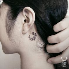 Small floral moon tattoo behind the left ear.