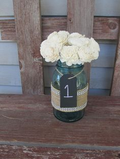 Mason jars with a little bit of country rustic and a little bit of bling!  The chalkboard table numbers fits right in. 6 Chalkboard mason jars wedding centerpiece table tags. $12.50, via Etsy.