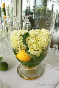 simple vase filled with some citrus fruits and topped with some cream colored flowers.