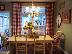 Love the red check fabric; the rush seats; sunflowers; wall clock; chandelier.  Could recreate this look -  djc