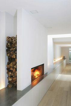 Le foyer de cet insert de cheminée est surélevé par rapport au sol, afin de le porter à hauteur des yeux pour l'observateur installé dans son fauteuil. Une niche dissimulée sur le côté permet de ranger une bonne quantité de bûches.