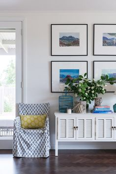 'The Albert Namatjira watercolours were a gift from John's father, they take pride and place in the living room, and have lots of sentimental value' – Sarah. white timber louvre buffet in the lounge room from Sasson Home. Cushion and chair cover by Canvas Home. Photo - Brooke Holm, production – Lucy Feagins / The Design Files.