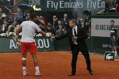 Spain's Rafael Nadal shakes hands with a security guard who protected him when a demonstrator with a flare ran onto center court when playing compatriot David Ferrer in the final of the French Open tennis tournament, at Roland Garros stadium in Paris, Sunday June 9, 2013