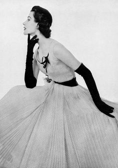 Myrtle Crawford in finely pleated, white muslin dress dotted in black, sleeveless bodice is decorated with black ribbon, black gros-grain belt holds pink rose, by Madeleine de Rauch, photo by Pottier, 1953