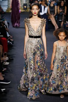 """Os já conhecidos """"vestidos de princesa"""" da marca brilham, cheios de volume mais aplicações e bordados; eles aparecem intercalados a looks mais ousados, muitos feitos em veludo, com grandes fendas, decotes profundos e transparências."""