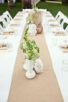 Burlap runner, white tablecloth, mason jar glasses, greenery, woven accents