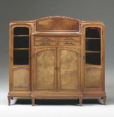 "Eugéne Gaillard (1862-1933) - Vitrine-Cabinet. Carved Walnut and Glass with Bronze Hardware. Circa 1913. 57-1/4"" x 62-1/2"" x 16"" (145.5cm x 158.8cm x 40.6cm)."