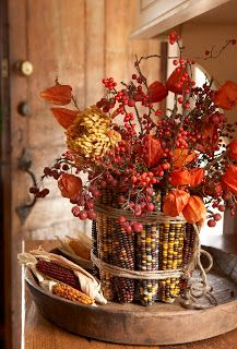 DiY Indian Corn Vase ::: Wrap a can with rubber bands. Then remove the husks from corn and simply slide the corn cobs in standing them upright. Cover the rubber bands with twine & fill with fall flowers like dahlias, mums, berries and asters.
