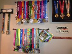 Simple, inexpensive way to hang medals. Use a curtain rod (under $6 at Walmart) and space how you like. Use hooks to hang bibs. Much less expensive than medal holders purchased online. #running #races #marathon