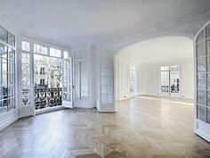 Parisian style living room - herringbone pattern wood floors, millwork, wrought-iron balcony.