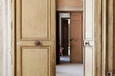 Beautiful antique wood doors. The decaying 18th century historic Chateau Gudanes in the South of France is being restored by its new owners. Limestone, stripped wallpaper, antique doors, shutters, and so much more lovely to explore in this before and after renovation story.