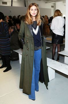 Olivia Palermo wearing an olive green long coat with wide leg jeans