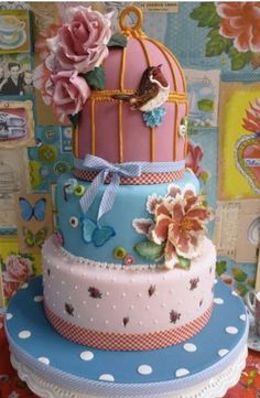 blue pink and white , multi tier celebration cake, birds nest on the top.