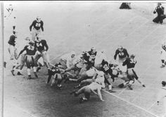 Texas' Pete Layden (#11) makes the lone score to beat A&M 7-0 in the 1940 classic in Austin. Aggie defenders in the picture include: (#43), Ernest Pannell (#54), Tommie Vaughn (#60), Chip Routt (#58), William Conatser (#49), and John Kimbrough (#39)