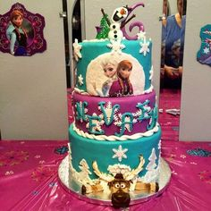 Disney Frozen Cake - White chocolate cake with white chocolate cream cheese frosting covered in homemade marshmallow fondant. Decorations hand made out of fondant. Edible image of Elsa and Anna, pasted on fondant. Disco dust sprinkled on snowflakes.