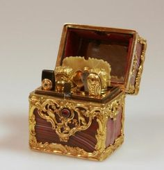 A Fine French Gold and Red Banded Agate Etui. Circa 1780. The hinged cover opening with an Amethyst button to reveal a fully fitted mirrored interior. The gold mounts stamped with a Hound and Pheasant amongst scrolling foliage and incorporating a gold on white enamel incription. 2JE ME FIE A VOTRE AMITIE''.5.3cm high. 4.2cm wide. 3.3cm deep.