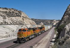 Site of Alray Tunnel, Cajon, CA 2014 - BNSF 7702 leads two further BNSF locos down Cajon Pass, more or less where Alray Tunnel used to be, which was daylighted when the third track was added. That's the UP (former SP Palmdale Cutoff on the left at the higher elevation). 18 March 2014.