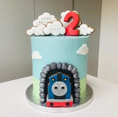 A towering cake coated in a smooth velvety buttercream in honour of all things Thomas the Tank Engine! With biscuit clouds adoring the cakes top and an incredible replica of Thomas at the cakes front. Thomas Birthday Cakes, Thomas Birthday Parties, Thomas Cakes, Thomas The Train Birthday Party, Pig Birthday Cakes, Novelty Birthday Cakes, Trains Birthday Party, 3rd Birthday, Birthday Ideas