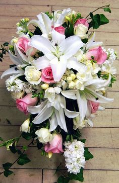 Cascade bouquet of white lilys with a little pink dotted thru out. Flower Factor