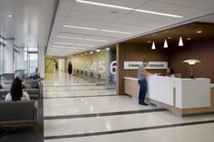 The patient registration area in the ancillary building uses a linear floor pattern made of terrazzo along with numbered wayfinding signage on divider panels to delineate individual spaces. A waiting area and information desk are adjacent to the area to create a supportive experience for patients and families. Photo: Credit: Photographs by David Wakely