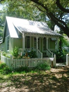 Green house with cute little porch, pretty roofline over