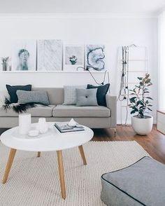 Stue, grå sofa med pyntepuder, plante, tæppe, billeder, stol og hvidt sofabord