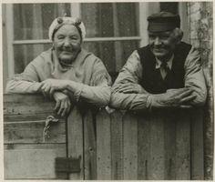 Schevenings echtpaar op het plaatsje voor hun huis; zij draagt een ijzer met boeken, parelspelden, een geplooide muts, een omslagdoek met gehaakte franje; hij draagt een overhemd met vest en heeft een zijde petje op het hoofd. 1931 #ZuidHolland #Scheveningen