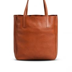 Medium Shopper Tote in pressed-back Horween Essex leather. Handcrafted with nickel-plated brass hardware, and featuring two open interior gusset pockets, canvas removable zip pouch with leather trim.