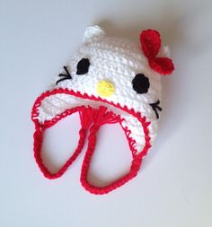 $15.00 - Baby white & red crochet Hello Kitty beanie hat with flaps and braids, size Newborn 0-3 Months, 3-6 Months or 6-12 Months. This hat looks just like the popular Hello Kitty character! Do you or your child love Hello Kitty? Show off your fandom by wearing this hat! It also makes a great Christmas gift, with the holidays coming up soon!