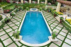 In dit tuinontwerp wordt het zwembad op een kunstige wijze vormgegeven door kunstgras en tegels te combineren.