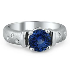The Nancy Ring: A brilliant blue sapphire glows in this modern estate piece. Three flush set, round brilliant diamond accents shine on either side of the center gem, creating a stunning mix of matte metal and sparkling diamonds (approx. 0.04 ct. tw.).