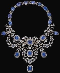Sapphire and diamond necklace, late 19th century.  It is of bow and foliate swag design, millegrain-set with variously cut sapphires and circular-, single-, cushion-shaped and rose diamonds. It detaches into 6 pieces so that the jewels can be worn separately.