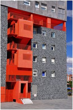 The bright and fun colors of the L shape on the building creates contrast again the rocky grey building. Colour Architecture, Facade Architecture, Amazing Architecture, Contemporary Architecture, Building Facade, Building Design, Facade Design, Exterior Design, Parasitic Architecture