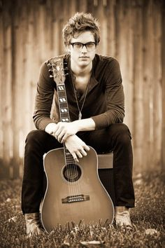 Cute nerd with glasses holding guitar