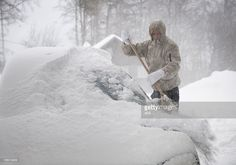 Stock Photo : Man freeing car from snow in a blizzard (XXXL)