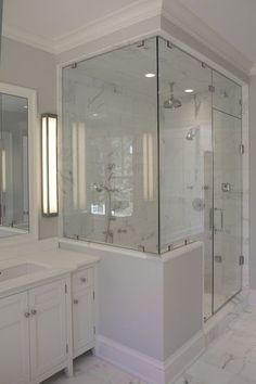 source: Jillian Klaff Homes Master bathroom with cool gray paint color, seamless glass shower with marble tiles shower surround, polished nickel rain shower head, white bathroom vanity and marble tiles floor. Half Walls, Half Wall Shower, Glass Shower, Steam Shower Enclosure, Bathrooms Remodel, Bath Remodel, Frameless Shower Enclosures, Small Master Bathroom, Bathroom Remodel Master