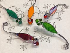 "A ""lounge"" of lizards. Glass and wire sculptures, each approx 7""."