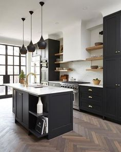 Wood herringbone kitchen floors contrast with stunning aesthetic against black kitchen cabinets, doors, and shelves.