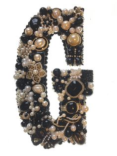 """G - Handcrafted Black & Pearl Letter Decor G Wall Art Created From Recycled Vintage & Modern Jewelry, G12. Add a bit of elegant charm to your home decor with this unique monogram wall art. The letter """"G"""" is handcrafted using recycled vintage and modern jewelry. Blacks & pearls are featured on this creation. Our letters are constructed on a custom made solid wood base that is 5/8"""" thick and measures approximately 10"""" tall x 7"""" wide. Hang by saw-tooth hanger on back. H11."""