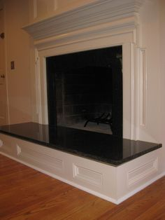 Raised paneled fireplace with granite surround and hearth